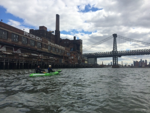 Volunteer Sally Attia, Esq. and Facilities Manager Pat Erickson paddling by the Domino Sugar Factory by the Williamsburg Bridge